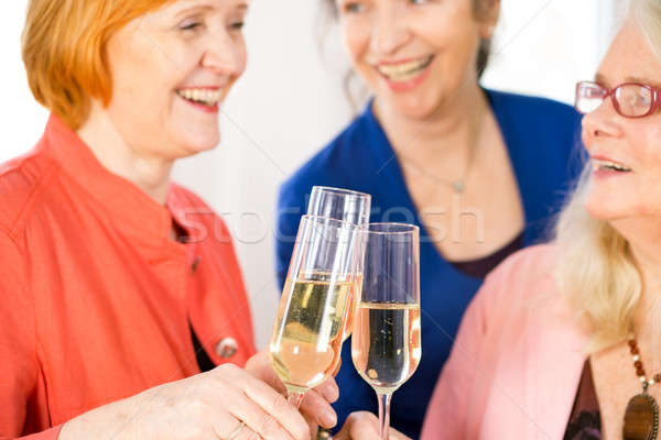 Glasses of White Wine Tossed by Happy Adult Ladies Stock photo © belahoche