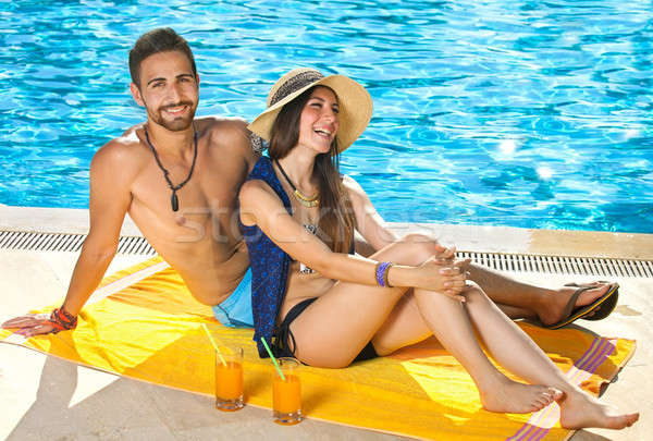 Attractive couple relaxing alongside a pool Stock photo © belahoche