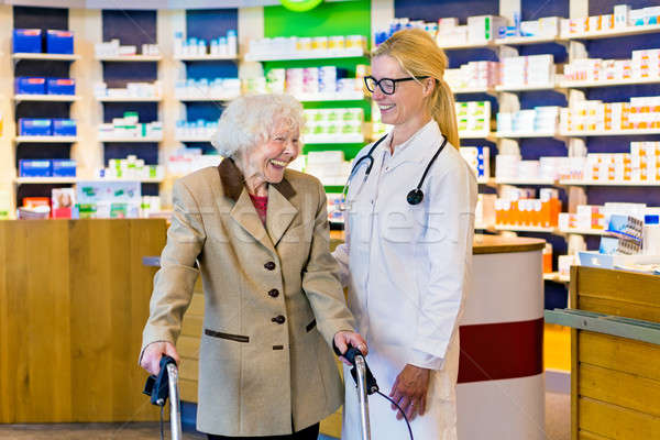 Senior woman and doctor laughing in pharmacy Stock photo © belahoche