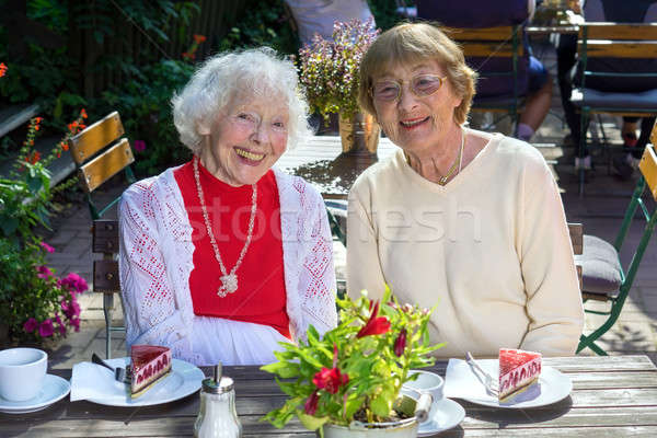 Laughing senior women seated with cake.  Stock photo © belahoche