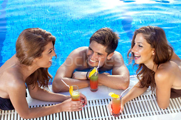 Guy flirting with two women at the swimming pool Stock photo © belahoche