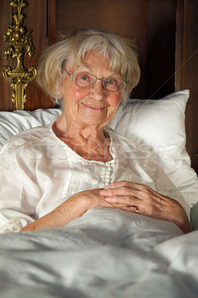 Happy senior lady relaxing in bed Stock photo © belahoche