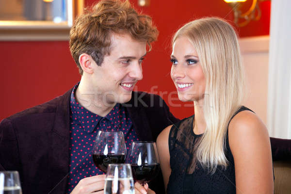 Happy couple celebrating with red wine Stock photo © belahoche