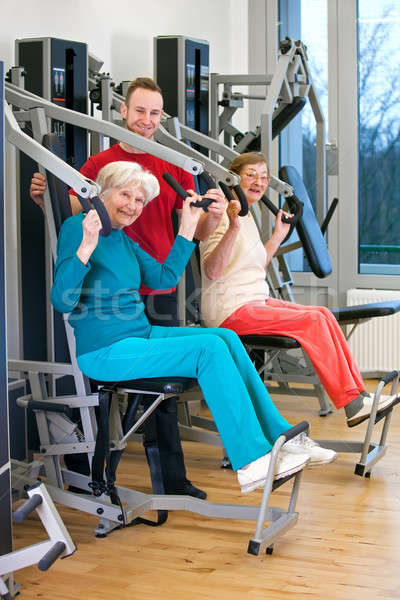 Happy Old Women at the Gym Assisted by Instructor Stock photo © belahoche