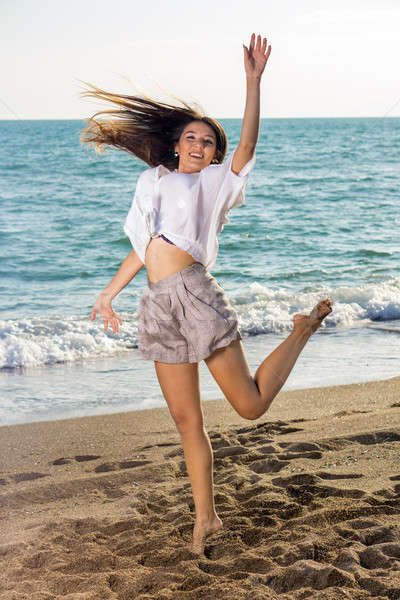 Young Woman in Funny Jump Shot at the Seaside Stock photo © belahoche