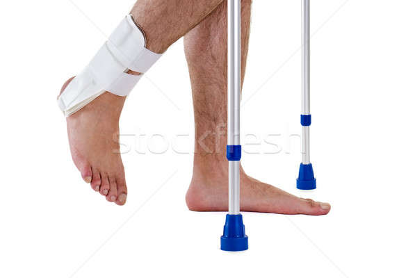 Man Wearing Ankle Brace Walking with Crutches Stock photo © belahoche
