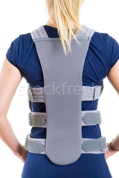 Woman Wearing Supportive Back Brace in Studio Stock photo © belahoche