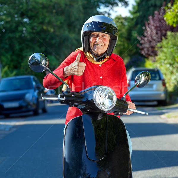 Smiling old lady on a scooter Stock photo © belahoche