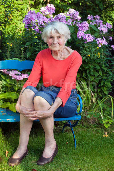 Stock photo: Smiling Old Woman Sitting on the Garden Bench
