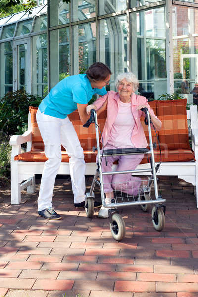 Senior woman being helped by a care assistant Stock photo © belahoche