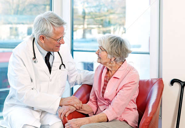Friendly doctor reassuring an elderly woman Stock photo © belahoche