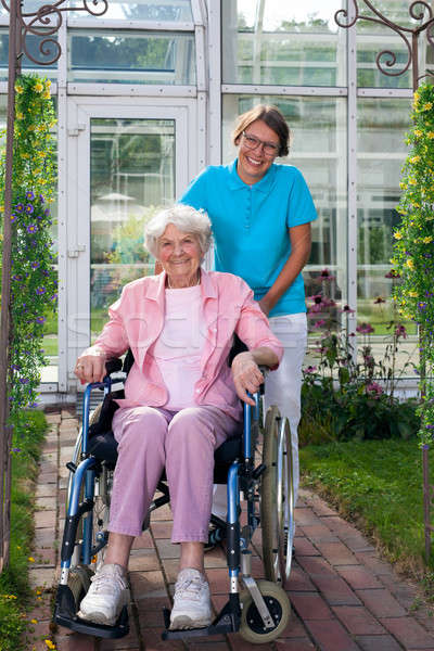Smiling happy elderly lady in a wheelchair Stock photo © belahoche