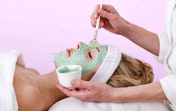 Beautician applying a thalasso face mask.  Stock photo © belahoche