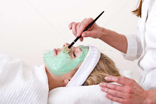 Beautician applying facial mask on the cheekbones.  Stock photo © belahoche