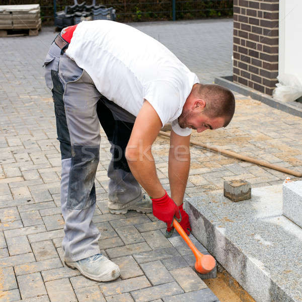 A worker creates a terrace of concrete paving stones.  Stock photo © belahoche