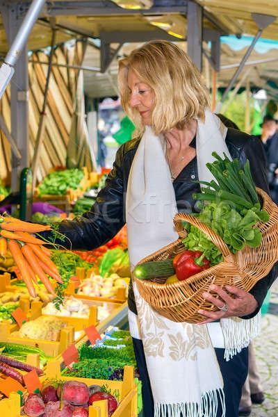 Woman selecting a bunch of fresh carrots Stock photo © belahoche