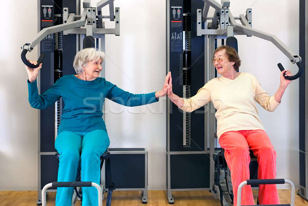 Old Ladies Exercising While Touching their Palms Stock photo © belahoche