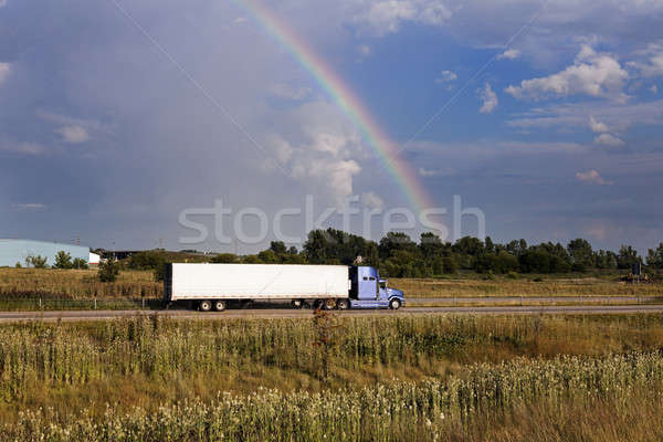 Semi truck driving under the rainbow Stock photo © benkrut