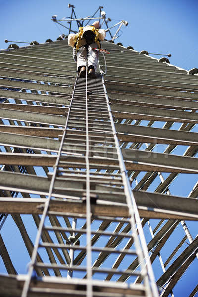 Climber ascending cell phone tower Stock photo © benkrut