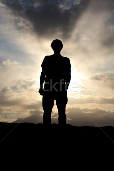 Back lit man before dramatic cloudy sky Stock photo © Bertl123
