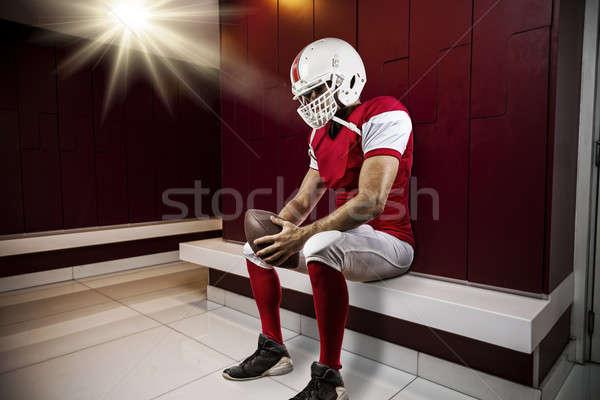 футболист красный равномерный сидящий раздевалка глазах Сток-фото © betochagas