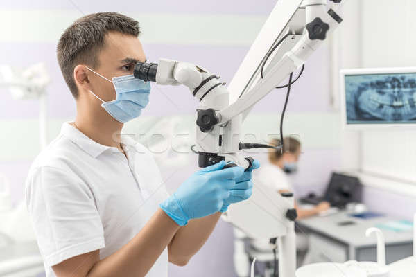 Dentist using dental microscope Stock photo © bezikus