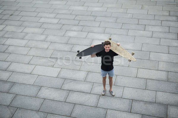 Young boy standing with two different longboard Stock photo © bezikus