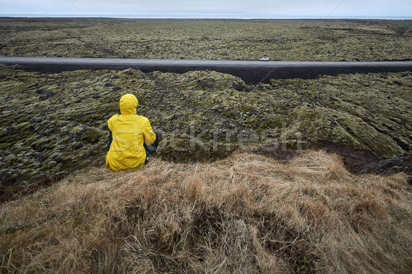 Man sits on cliff opposite country roadway Stock photo © bezikus