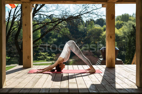Girl in downward facing dog pose Stock photo © bezikus