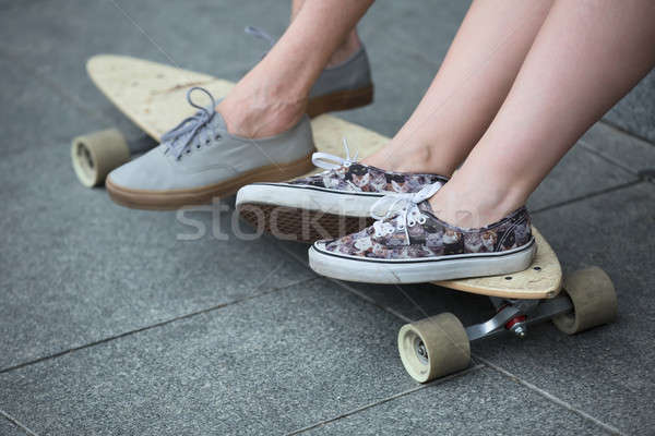 Feet couple of teenagers in sneakers on longboard closeup Stock photo © bezikus