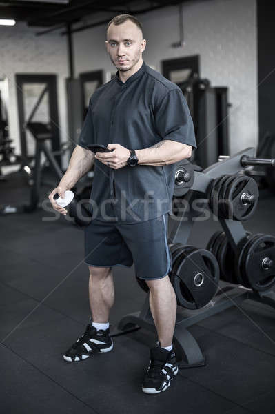 Muscular man has pause in gym Stock photo © bezikus
