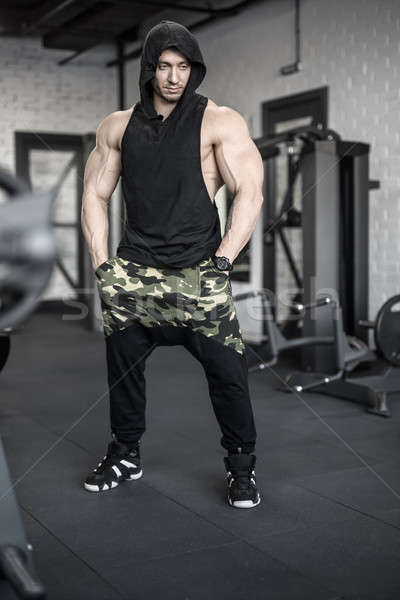 Strong man posing in gym Stock photo © bezikus