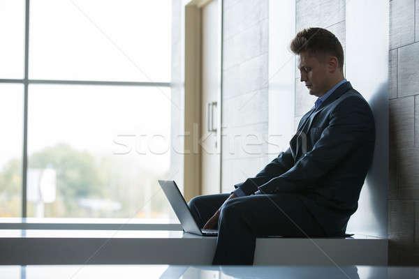 Business man sitting alone on a bench with laptop Stock photo © bezikus