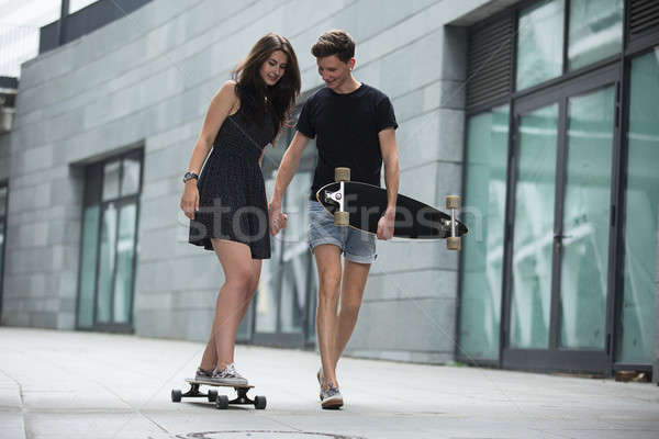 Young pair in love of stylish teenagers ride longboards  Stock photo © bezikus