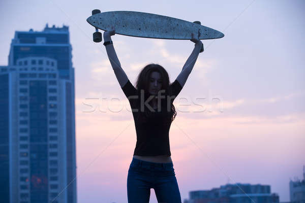 Stylish girl in jeans holding aloft longboard  Stock photo © bezikus
