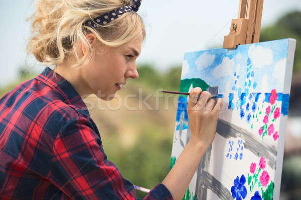 Beautiful blonde woman artist paints a colorful picture. Stock photo © bezikus
