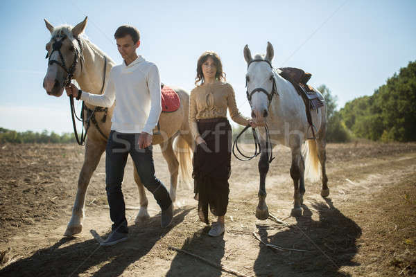 Young couple walking in a picturesque place with horses Stock photo © bezikus