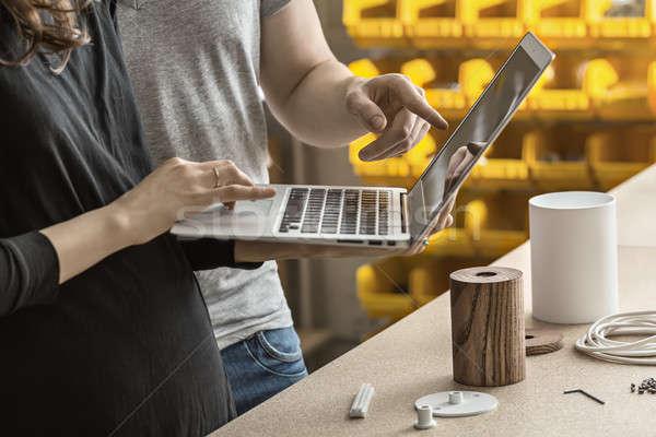 Man and woman using laptop in workshop Stock photo © bezikus
