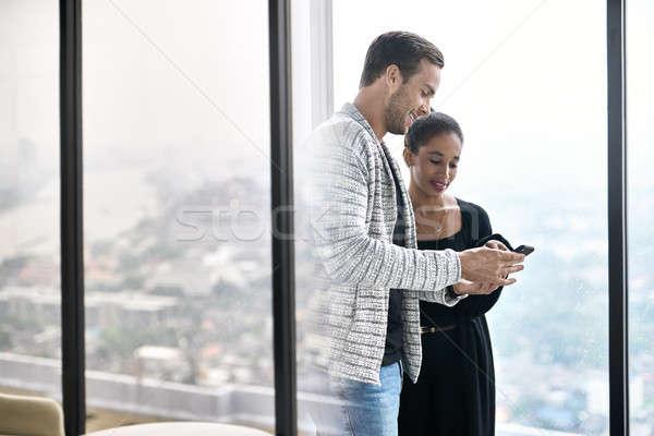 Casal sorridente posando grande windows olhando Foto stock © bezikus