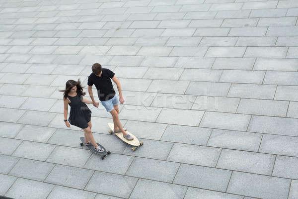 Young pair of stylish teenagers ride longboards Stock photo © bezikus