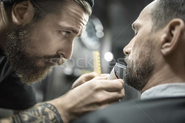 Trimming beard in barbershop Stock photo © bezikus
