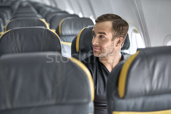 Stock photo: Handsome guy in airplane