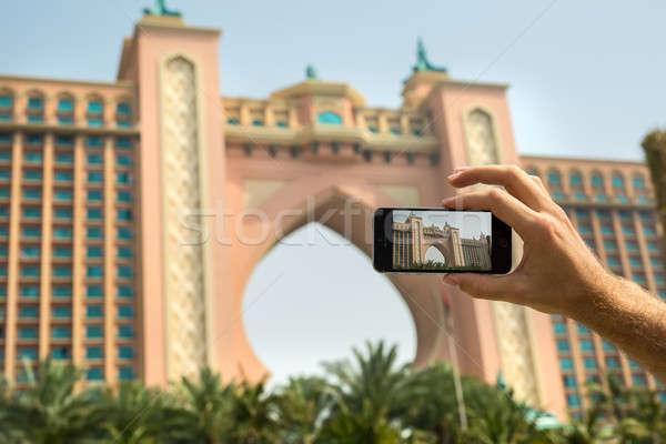 Stock photo: Hand tourist takes a picture of the hotel Atlantis Dubai on mobi