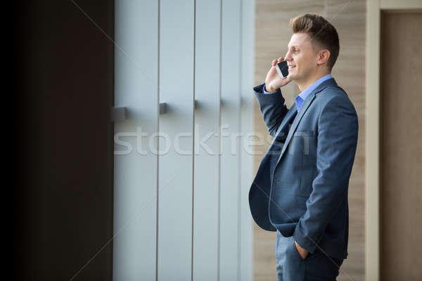 Férfi telefon aranyos üzlet öltöny ablak Stock fotó © bezikus