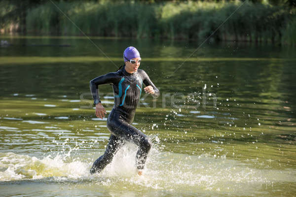 Stock photo: Sportive girl runs on the water