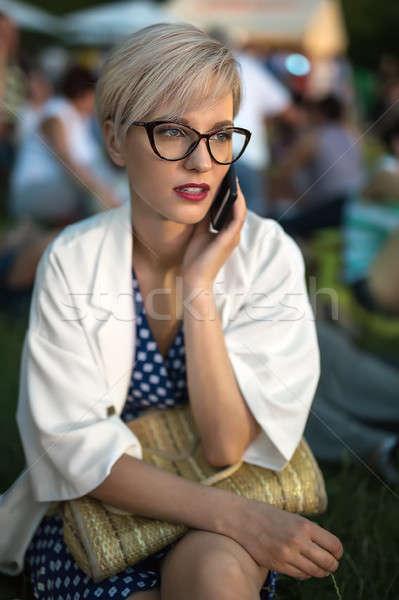 Blonde talks on cell outdoors Stock photo © bezikus