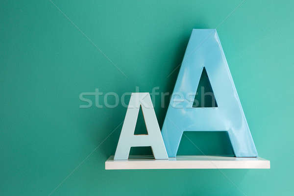 Letters A small and big size turquoise color on a white shelf. Stock photo © bezikus