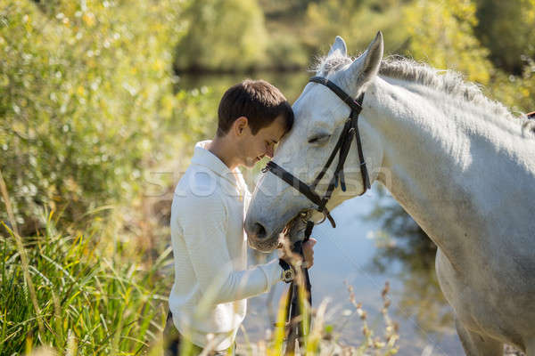 Man stands near the lake with a horse Stock photo © bezikus
