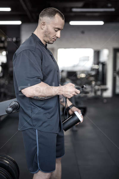 Muscular man has pause in gym Stock photo © bezikus