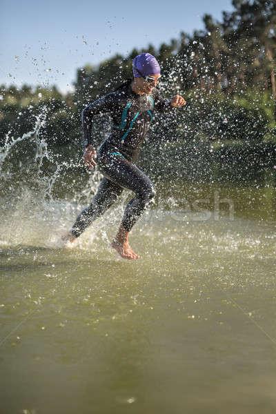 Sportive girl runs on the water Stock photo © bezikus